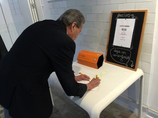 El Embajador de Honduras firma en el libro de visitas de la exposición.